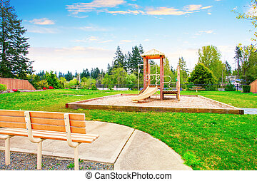 Backyard area with wooden play set for kids with swings and...