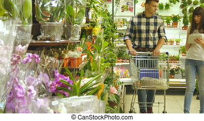 Young beautiful couple with supermarket trolley are walking and choosing indoor plant in the shopping mall. Woman is using tablet pc to check shopping list