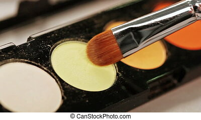 Makeup brush moving over multicolor eye shadows palette