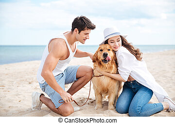 Couple sitting and hugging their dog on the beach - Happy...