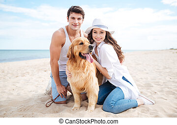 Couple with their dog on the beach in summer