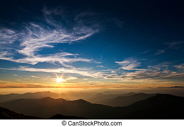 Magnificent sunset sky over silhouette of the mountains
