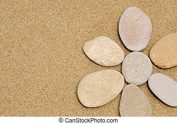 stone flower - flower made with stones on a sand background
