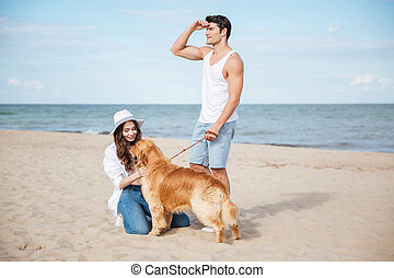 Couple in love playing with their dog on the beach - Young...