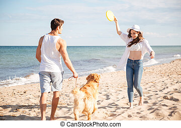 Young beautiful couple playing with their dog on the beach -...