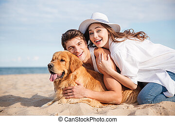 Couple with dog laughing and having fun on the beach