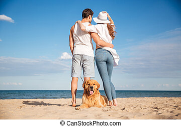 Couple standing and hugging while their dog lying on beach -...