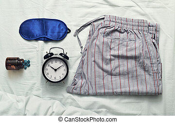 sleep mask, sleeping pills, alarm clock and pajamas -...