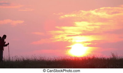 Silhouette of backpacker on sunrise background - Small...