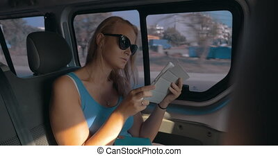 Girl with touch pad traveling by car - Young woman in...