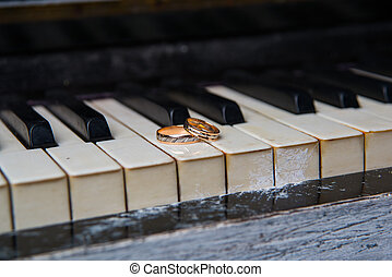 wedding rings lie on black and white keys of the piano