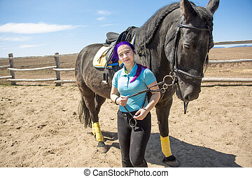 Beautiful teen girl on the farm with her horse.