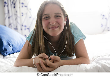 Pre teen girl is relaxing in the bed and listening to music with earphones