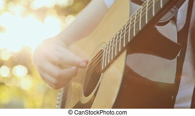 Teen girl playing acoustic guitar, close up