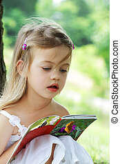 Child Reading - Little girl sits outdoors under a tree...