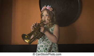 A little girl is playing saxophone in a cozy cafe - Music -...