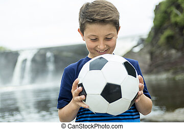 Two young boy outdoors with soccer ball smiling