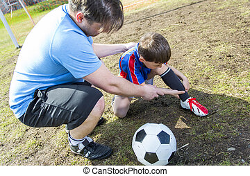 man with child playing football on pitch - A man with with...