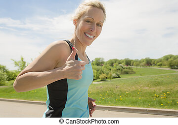mature woman running outdoors in the park - A mature woman...