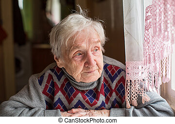 Elderly woman in a sweater looking out the window sitting at...