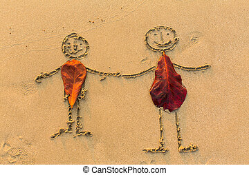 Couple of people figures drawn by hand on the beach sand.