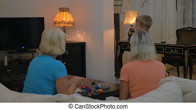 Boy dancing for grandmothers at home - Happy boy giving a...