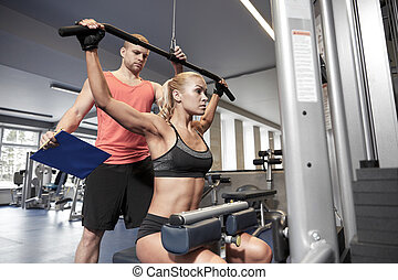 man and woman flexing muscles on gym machine - sport,...