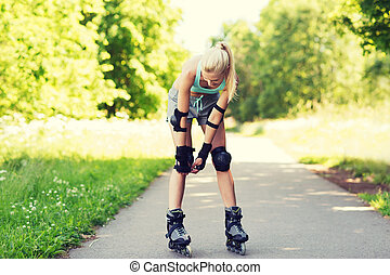 happy young woman in rollerskates riding outdoors - fitness,...