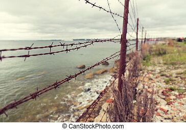 barb wire fence over gray sky and sea