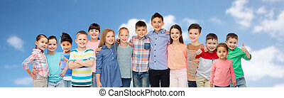 group of happy children hugging over blue sky