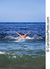 Swimming in the sea - A muscular man swims in the water of...