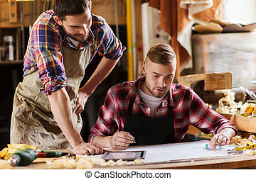 carpenters with ruler and blueprint at workshop -...