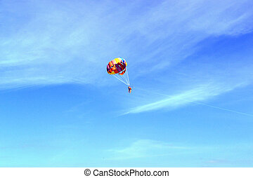 Skydivers On Colorful Parachute In Sunny Sky