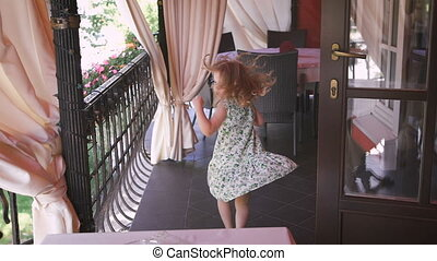A happy little blonde girl is jumping in the balcony. -...
