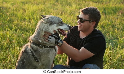 Man stroking a dog Husky.