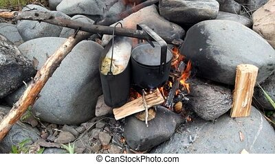 Pots of food boiling on a camp fire in the summer