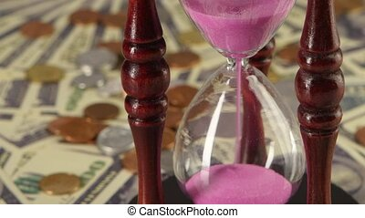 Hourglass standing on coins and banknotes. Close up -...