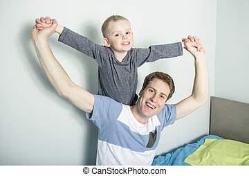 father play with his son boy on the bed at home