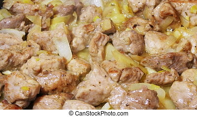 Pork meat pieces roasted on frying pan with onion