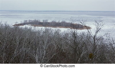 Ice-covered river with island winter landscape, panning...