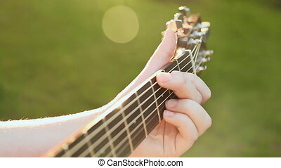 The girl plays a guitar, close-up fretboard guitar. - The...