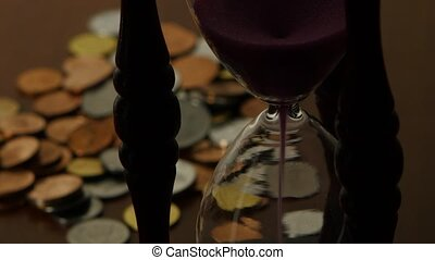Hourglass on coins background. Close up - Hourglass on coins...