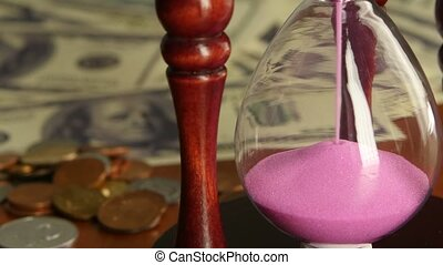Pink hourglass. Close up - Pink hourglass, sand flowing...