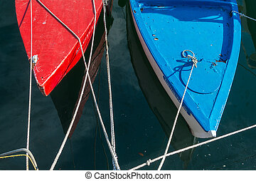 Fishing boats - Empty red and blue wooden boat moored in...
