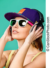 earphones - Modern young woman enjoys listening to music in...