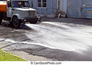 Water truck watering the asphalt at a manufacturing plant...