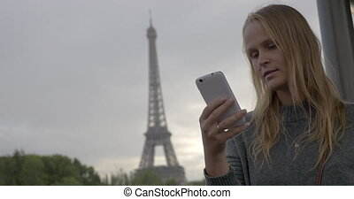 Woman using mobile and taking shot of Eiffel Tower