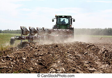 plowing a powerful tractor - power tractor plowing a field...