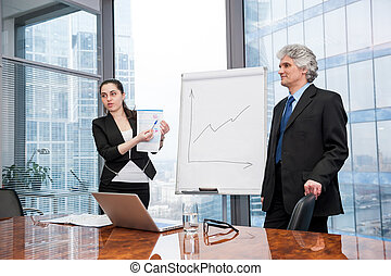 Young business woman and mature man making a presentation