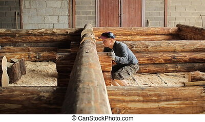 A man inspects beam house on the accuracy of the installation. Wooden house half built